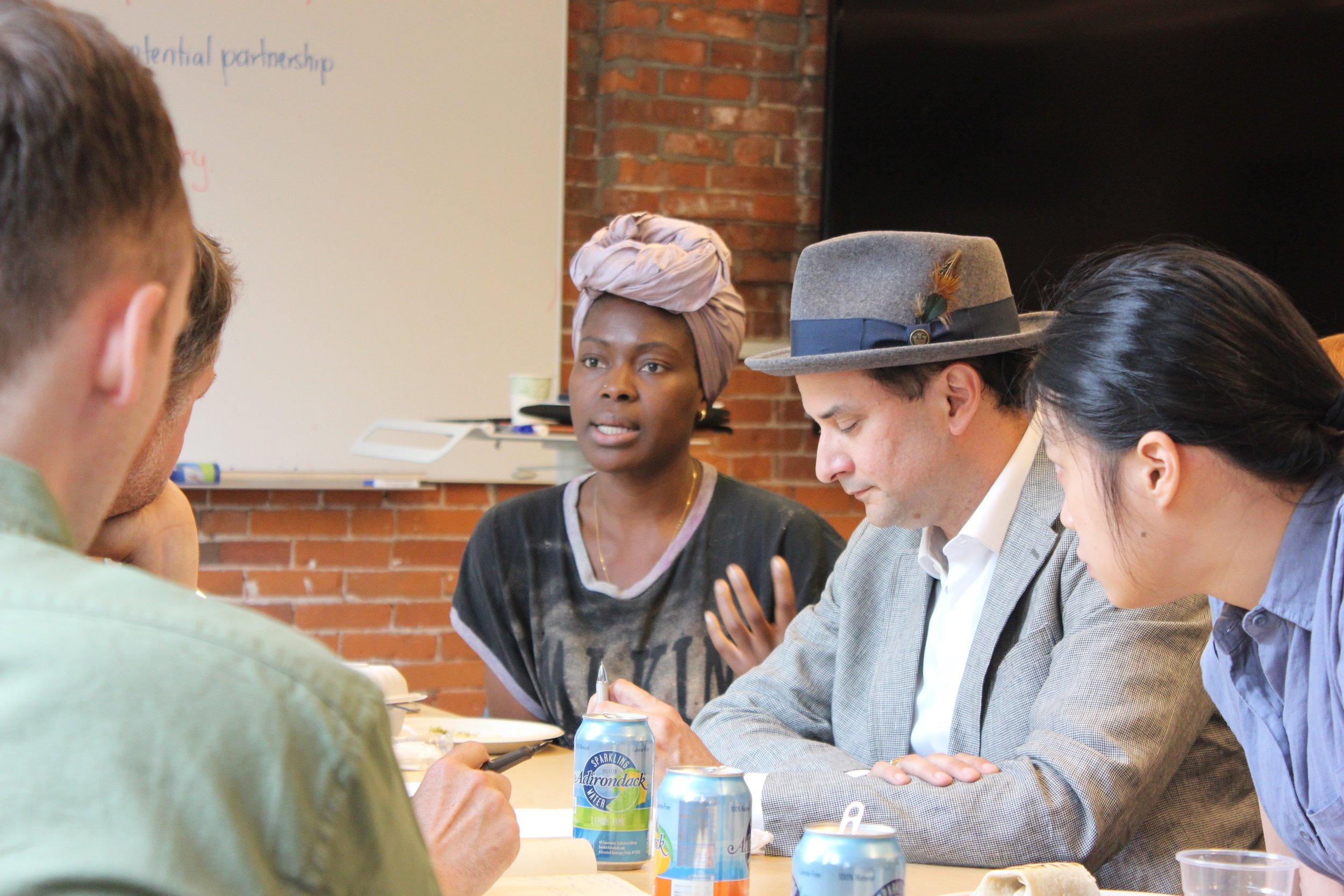 Siyonbola, center, speaks during a lunch with mentors.