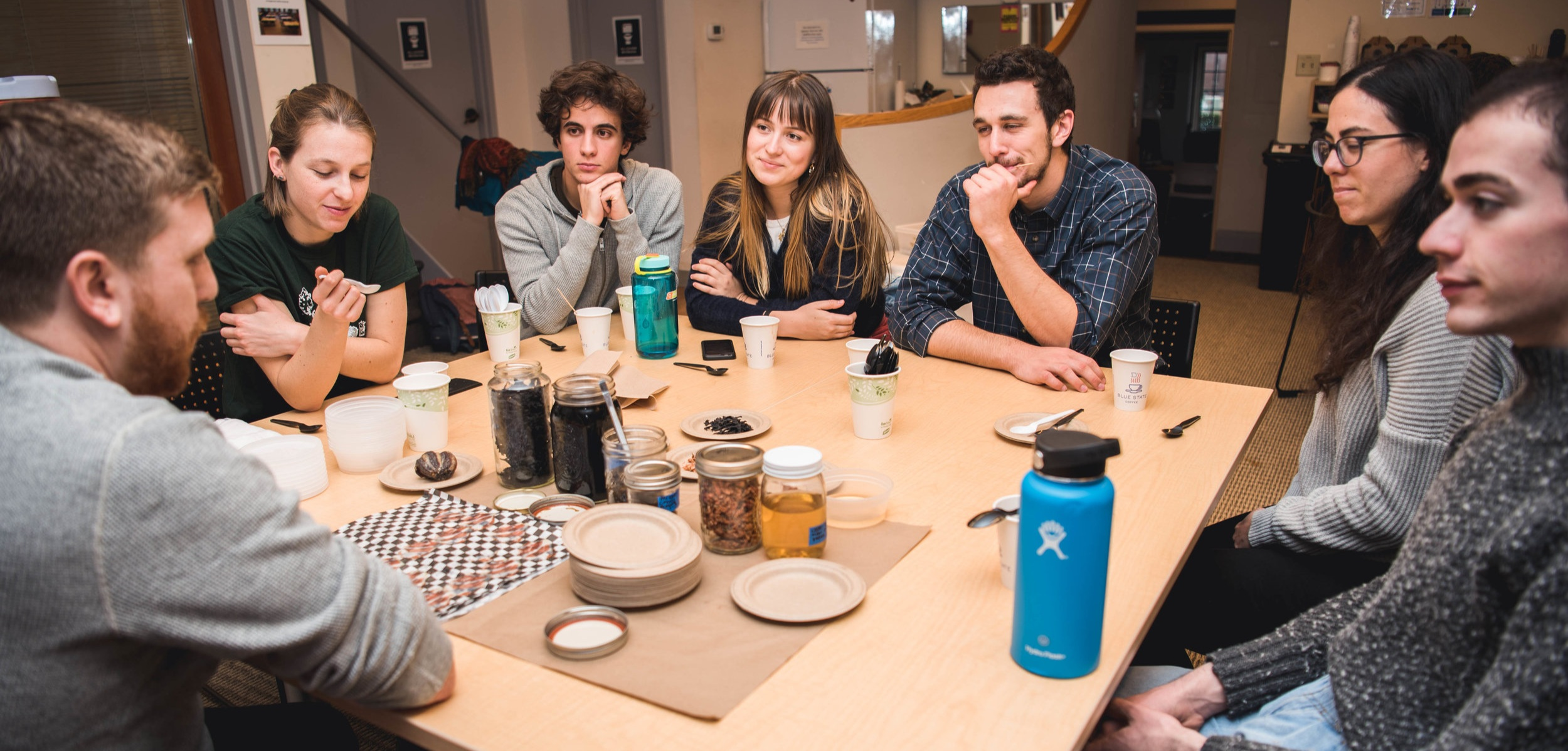Students around table with food products