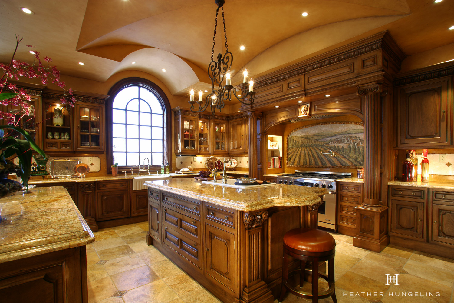 This amazing estate home has the ultimate luxury Tuscan-style kitchen, featuring Clive Christian cabinetry. Designed by Heather Hungeling