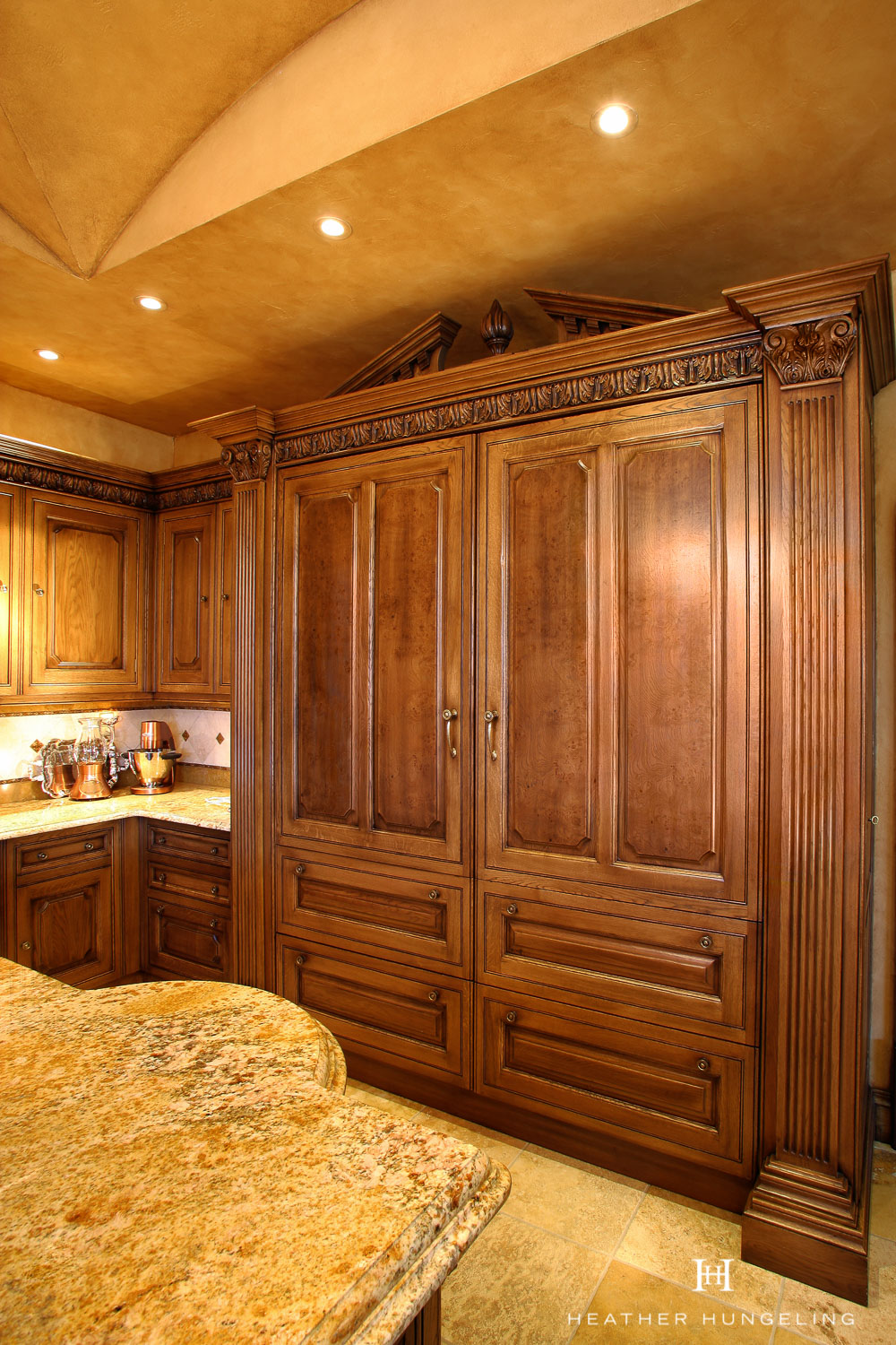 Double paneled Sub Zero refrigerator and freezers are dressed up with fluted pilasters and a pediment in this Clive Christian kitchen.