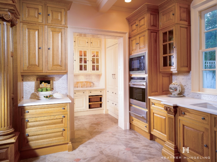 An adjacent walk-thru pantry area serves as an additional work zone for small countertop appliances and a coffee station. Cabinetry by Clive Christian in Antique French Oak. Designed by:  Heather Hungeling Design