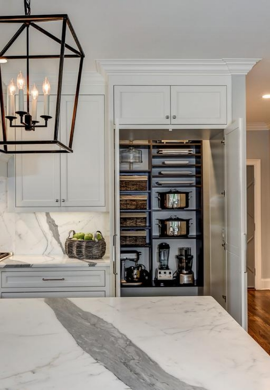 A void in the wall behind the cabinetry was utilized to turn a pantry cabinet into a hidden walk-in pantry - giving lots of storage for small appliances and cookware.  Source: Keystone Millworks via  DecorPad