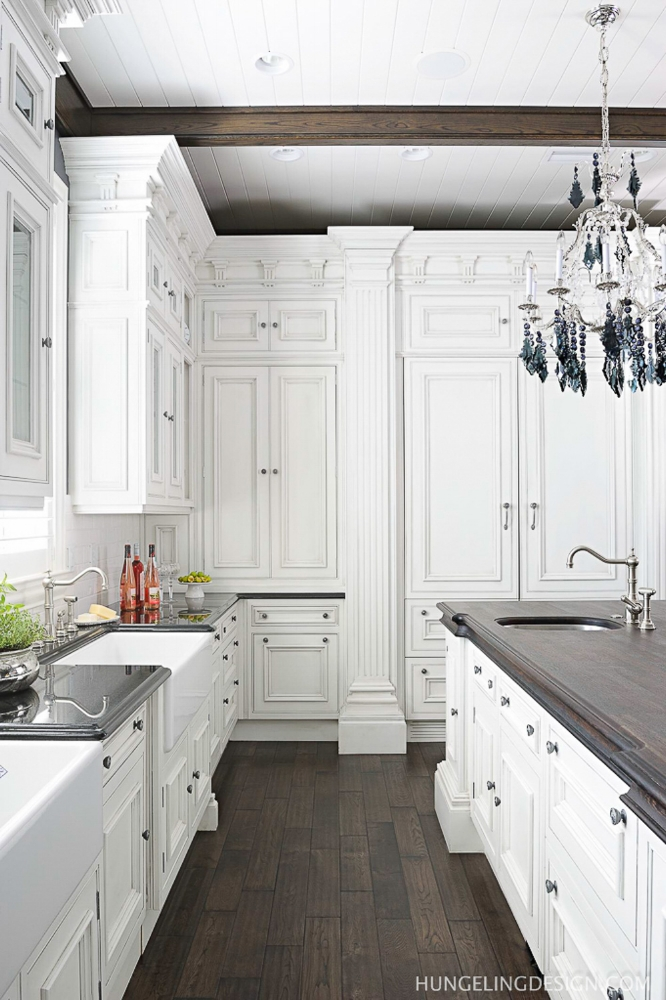 Luxury white kitchens should always have thoughtful places to conceal countertop appliances out of site. This kitchen features a dresser with pocket doors for stashing the food processor and other little appliances, while a lift-up shelf in the island holds the stand mixer.