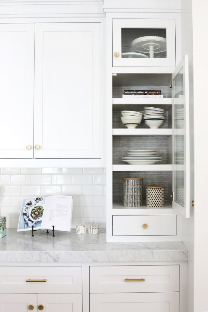 How to Make Your Kitchen Beautiful with Pretty Cabinet Details, Part 1 (Cabinet Interiors).  Studio McGee uses a soft gray grasscloth to provide an additional layer of interest to several glass cabinets. #kitchencabinetdetails.