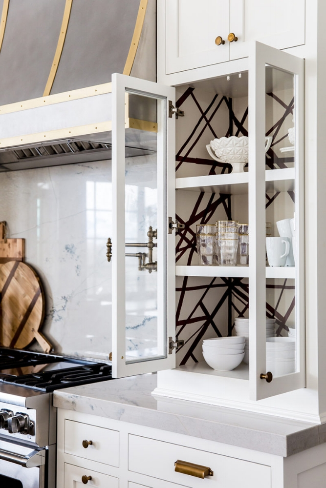 How to Make Your Kitchen Beautiful with Pretty Cabinet Details, Part 1 (Cabinet Interiors) . Alice Lane Home designed this stunning kitchen for a fashion forward lifestyle blogger. A Kelly Wearstler graphic wallpaper was applied to the interior of several focal point glass cupboards to give the room an edgy, but crisp look. #kitchencabinetdetails.