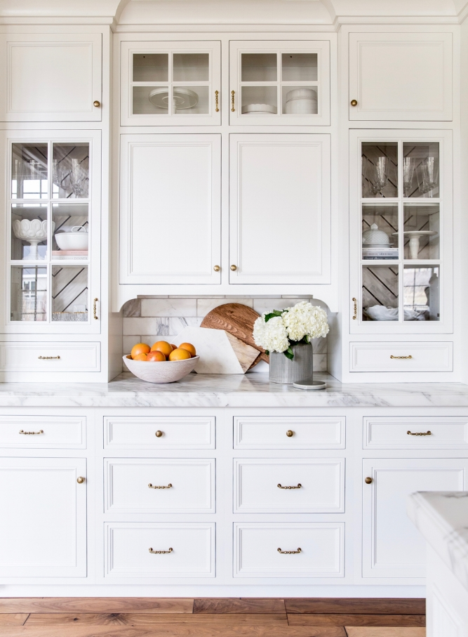 How to Make Your Kitchen Beautiful with Pretty Interior Details.  In this beautiful, feminine, white kitchen designed for the fashion blogger behind Pink Peonies, the designer used a pretty chevron pattern inside of the glass cabinetry. #kitchencabinetdetails.
