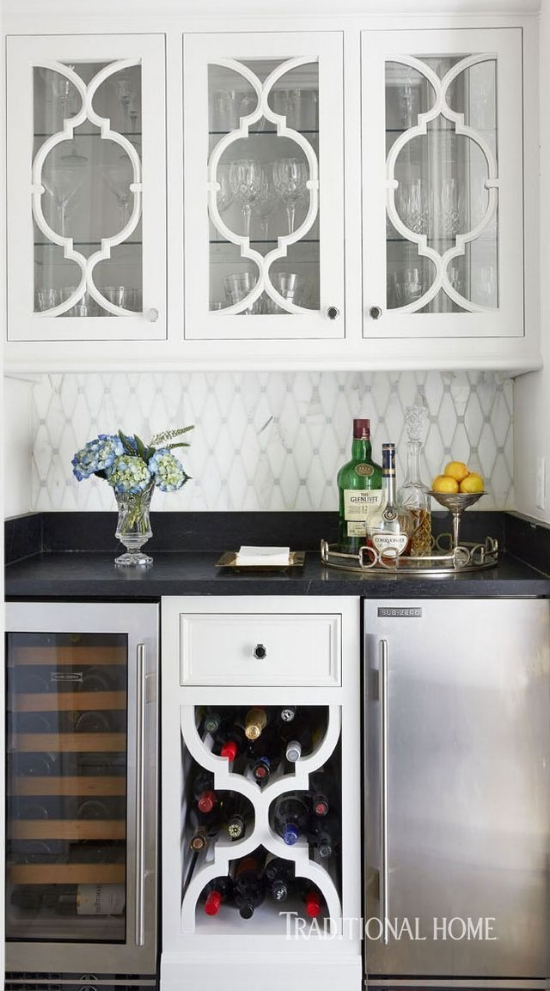 The designer, Dana Wolter, created a custom muntin pattern for this kitchen's glass cabinet doors, and reflected the same detail in the open cabinet on the bottom.