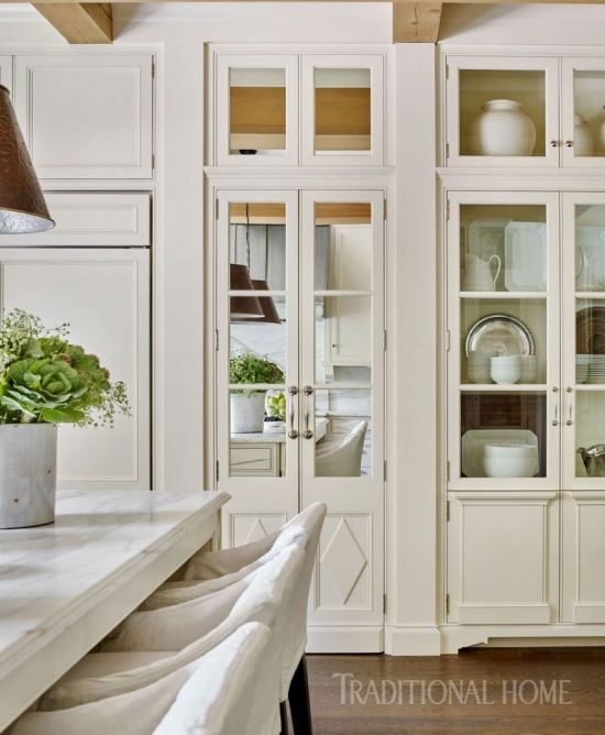 A set of mirrored doors (concealing a pantry) sit right next to a row of tall, glass cabinet doors, but they blend together so well that your eye hardly picks up on it.