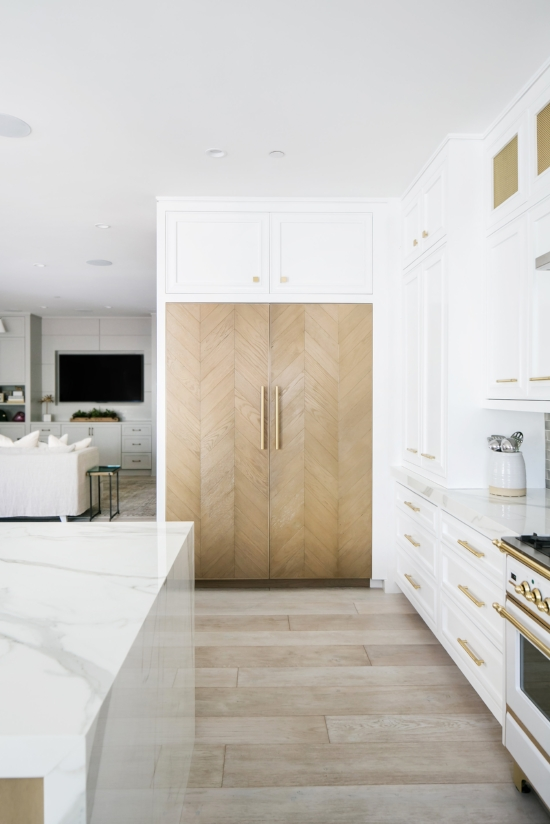 Light-stained oak parquetry panels accent the refrigerator in this two-tone kitchen design by Erica Bryen Design. Parquetry or Marquetry are just a few of many ways in which you can add pretty details and unique cabinet door styles to transform your kitchen design.