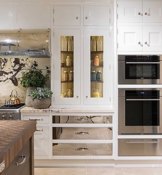 Polished stainless or nickel drawer fronts on either side of the range visually elongate the cooking zone. This is one of many ways that you can add drama to your next kitchen with stunning cabinet door styles.