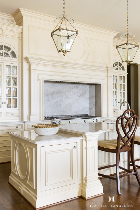 A circular shape featured on the island end panels is repeated on the panel above the range. This concept could easily be incorporated into cabinet door styles as well.