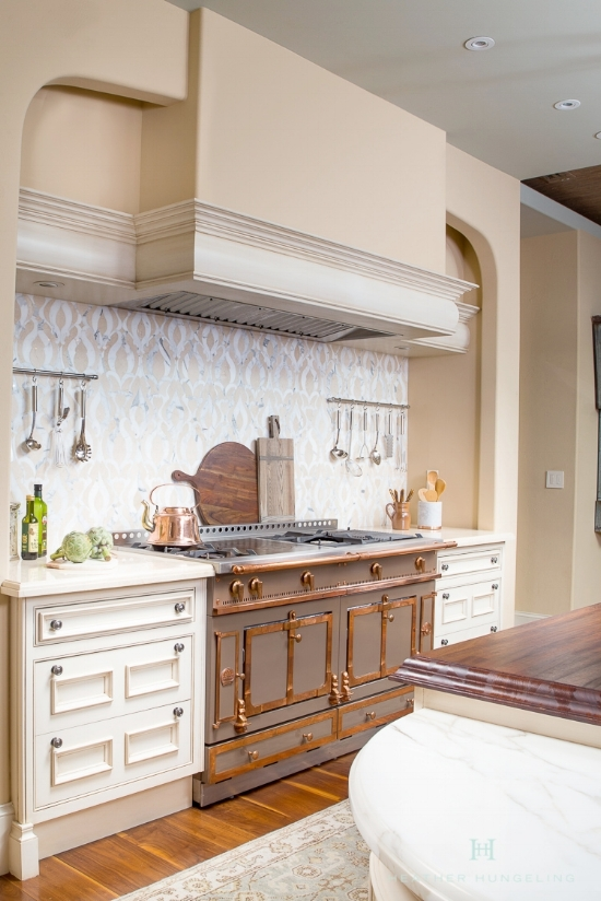 "Benjamin Moore's ""Muslin"" is a perfect warm, neutral color for these cream kitchen cabinets."