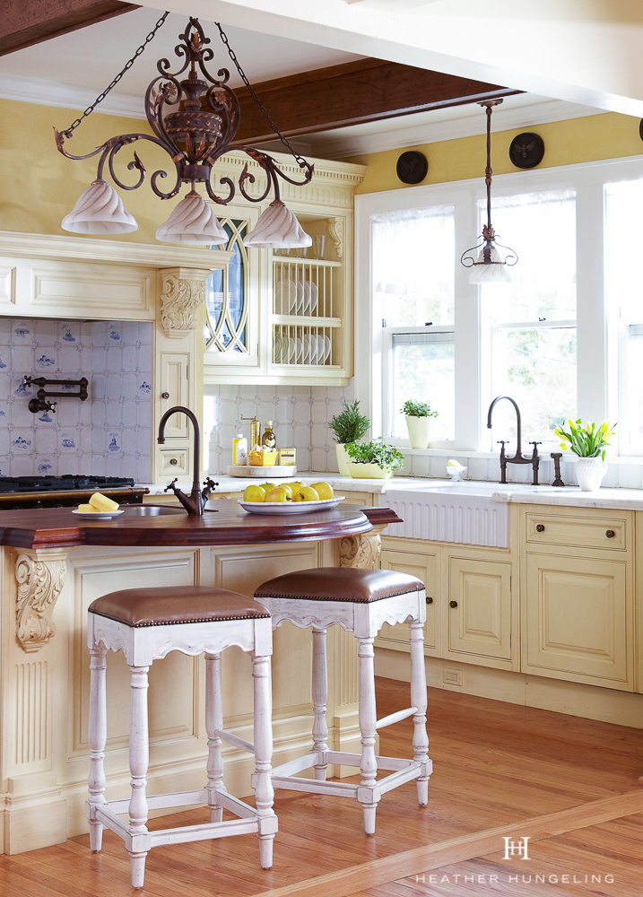 A small, but functional island met the homeowner's needs in this compact, vintage kitchen. Adding to the charm is a fluted farmhouse sink and a black CornuFe. Cabinetry by Clive Christian in Antique Cream.