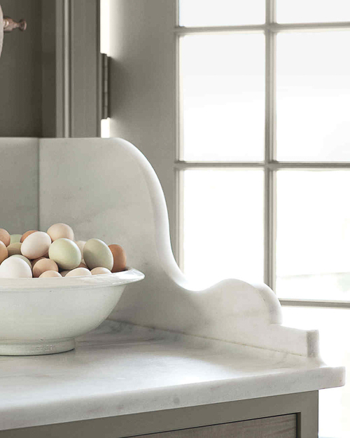 Martha Stewart created this beautifully scalloped marble edge bracket as a side wall to prevent messy spills when someone enters/exits the adjacent door. Beautiful Kitchen Marble Ideas.