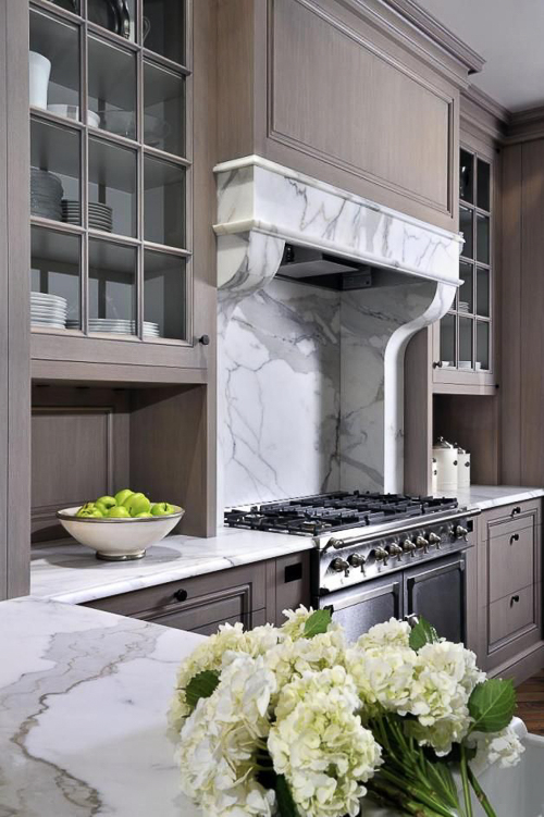 While marble range hoods are trending, they are typically more contemporary in design. I love this one by Peter Block. It references the lines and character of an Antique Marble Fireplace but is ideally suited to serve as this range hood. Works well with the paneled cabinetry. Kitchen Marble Ideas.