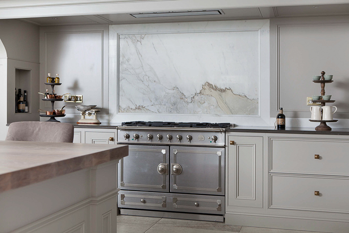 A beautiful marble backsplash behind the Cornu Fe range is complemented by the paneled cabinetry on either side. Kitchen Marble Ideas.