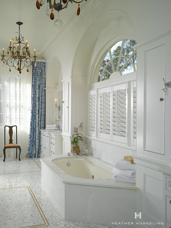 The full-length blue & white draperies add elegance and softness to this classic white bathroom. The undermount tub sits beneath a traditional arched window, while his & her vanities reside beneath matching arches on either side of the tub. See more beautiful Master Bathtub Ideas. #luxurybathrooms, #traditionalbathroom, #whitebathrooms, #clivechristian