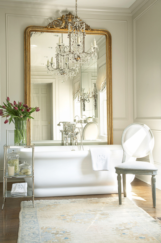 I love the designer's use of an over-sized mirror leaning up against the wall behind this freestanding bathtub. Not only does it help to reflect light around the room, but it creates a dramatic focal point since there is no window above the tub. See more Master Bathtub Ideas. #luxurybathrooms, #traditionalbathroom  Designer: Amy Morris Interiors