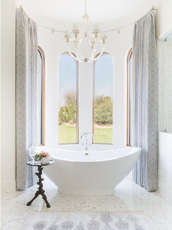 The most stunning bathtub settings are ones in which the designer uses his/her artistic eye to pair the architecture of the room with a complementary tub shape. This stunning bathroom by Bria Hammel Interiors does this so perfectly. See more beautiful Master Bathtub Ideas. #luxurybathrooms, #traditionalbathroom, #whitebathrooms