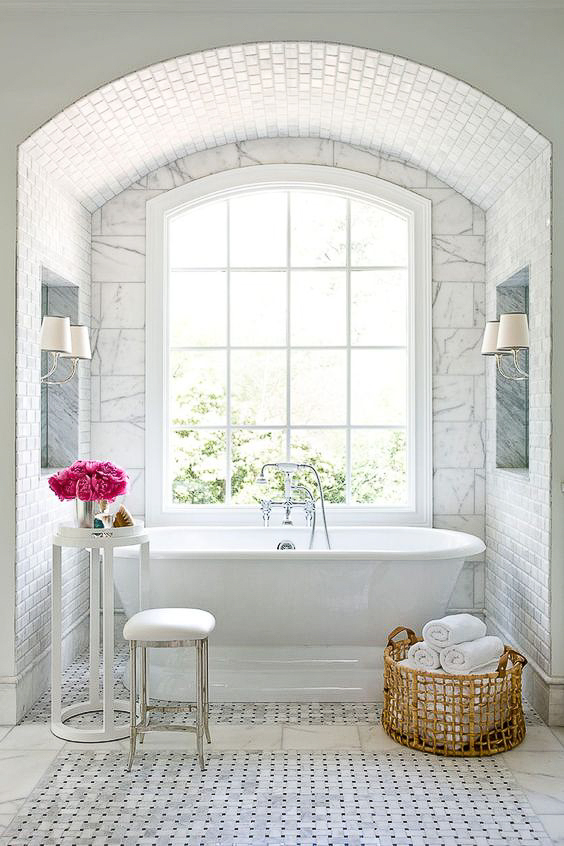 Creating a barrel arch over the bathtub beautifully frames up the view of a great window and tub combination. It also allows you an opportunity to showcase some stunning tile work. See more Master Bathtub Ideas. #luxurybathrooms, #traditionalbathroom, #whitebathrooms