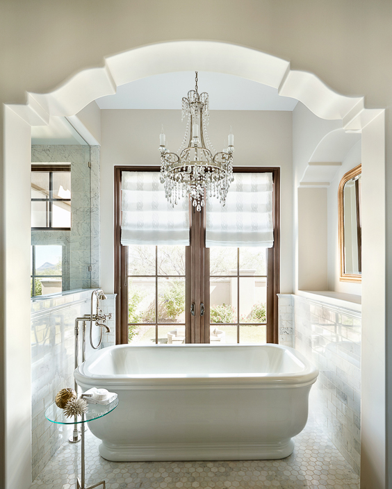 If you have a first-floor bathroom, consider french doors in your master bathroom instead of a window. I love how this designer exquisitely framed up the view with the intricate arch and freestanding tub. See other Master Bathtub Ideas. #luxurybathrooms, #traditionalbathroom, #whitebathrooms