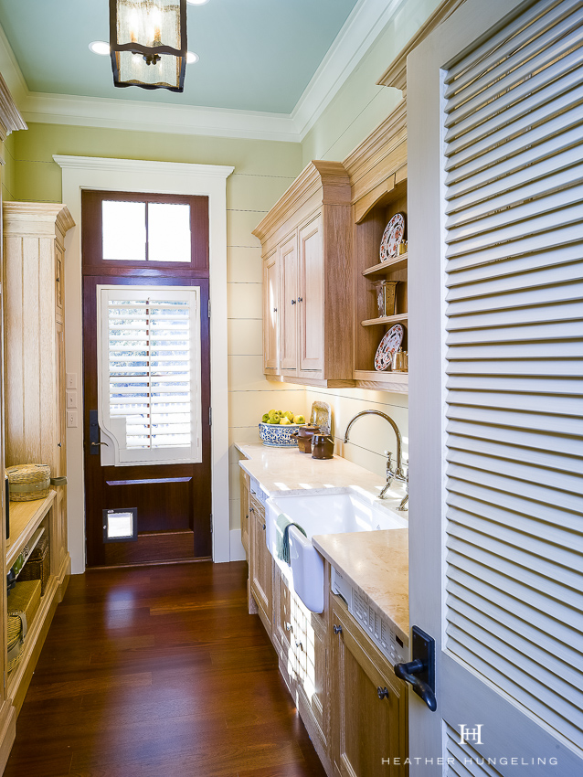 Haint blue ceilings are a common feature in a Lowcountry home. This laundry room features a blue ceiling with sage green walls and cerused oak cabinetry. Cabinetry by Clive Christian. #laundryroomideas, #clivechristian