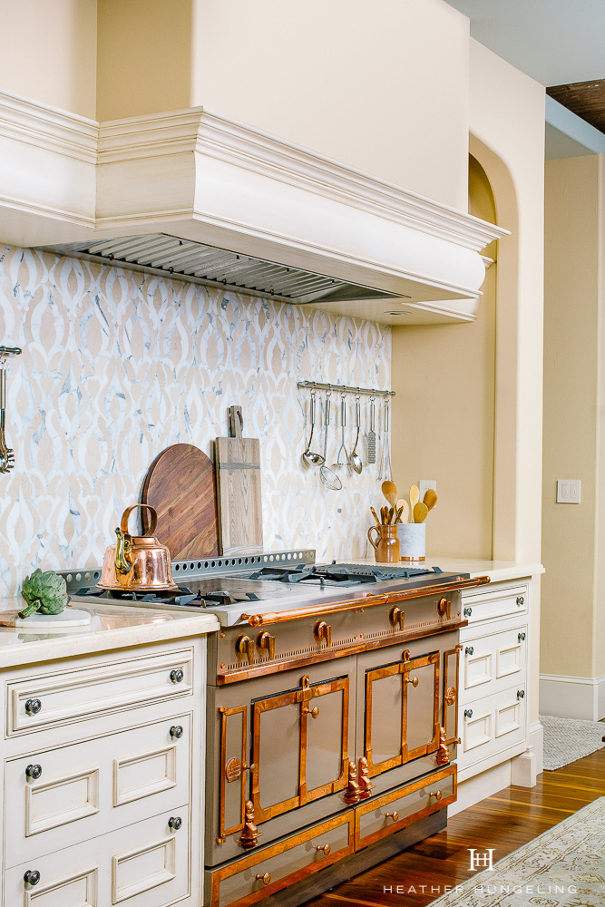 Willow Lane Project Reveal: A La Cornue in Cocoa with brass trim sits inside of this pretty little nook, with a simple arched range hood design and a water-jet-cut marble, patterned backsplash. Find out how I created a double island kitchen to solve many of this home's design challenges. #luxurykitchens, #lacornue, #kitchenlayout, #clivechristian.