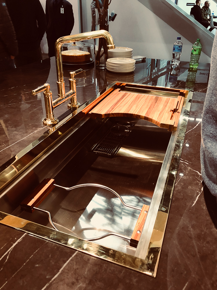 "Kallista's Multiere 45"" sink in stainless steel is not a new kitchen product for 2019, but they served it up in style at KBIS by displaying it with their Quincy faucet in unlacquered brass and a custom trim around the flange of the sink."