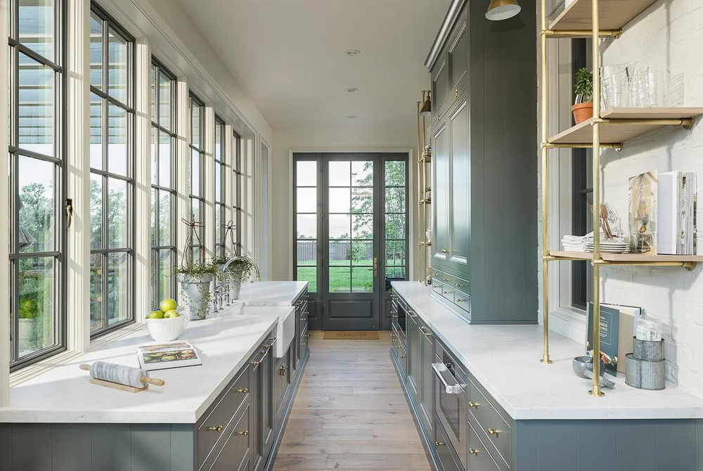 A spectacular prep kitchen by architectural firm Jackson & Leroy. They have cleverly positioned windows on the right wall to allow the light from this sunny little area to be shared with the main kitchen. Keeping the room light-filled and inviting is the key to creating a prep kitchen that you'll actually want to use.  #kitchendesign #luxurykitchendesigner #butlerspantryideas #kitchenlayouts
