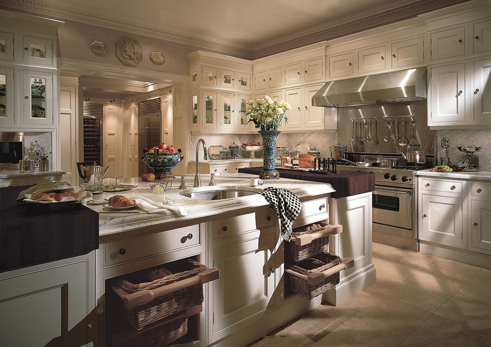 This beautiful kitchen by Clive Christian Furniture Company features a wide, cased opening to the smaller prep kitchen - lined with refrigerators, wine coolers, and pull-out pantries. The ability to house additional refrigeration is one of the most significant benefits of having a prep kitchen. Often, it can be challenging to work in multiple units into the design of the main kitchen, but positioning them inside of an adjacent room solves that problem.  #kitchendesign #luxurykitchendesigner #butlerspantryideas #kitchenlayouts