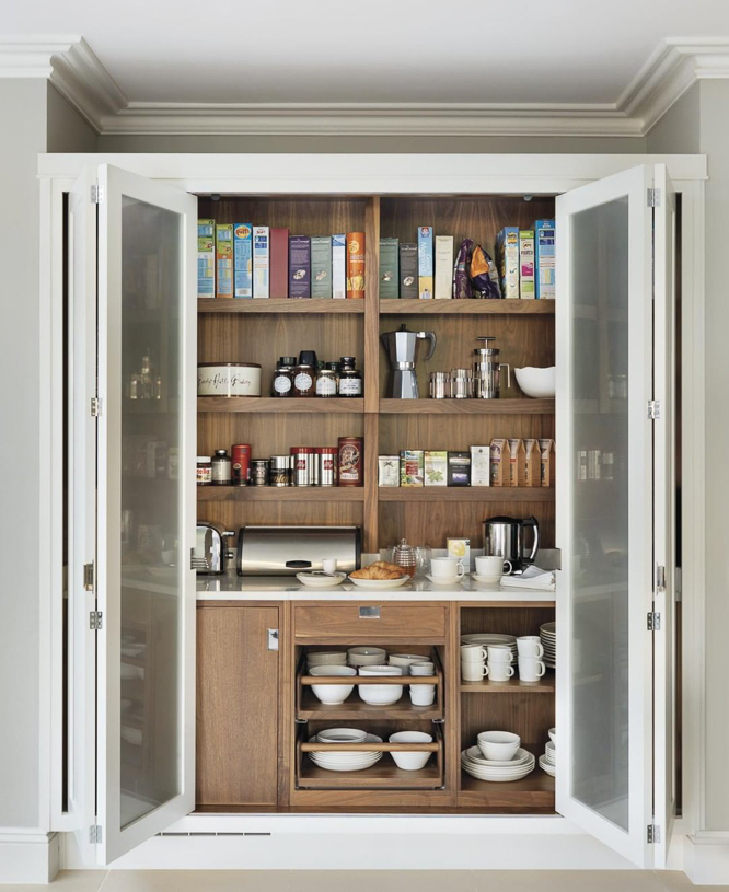 Smallbone of Devizes outfitted this beautiful larder with a mini-prep kitchen. A very attainable way to integrate the function of a prep kitchen into a smaller home. Bi-fold doors can be neatly stowed out of the way when the area is in use, but quickly closed up when not in use…allowing the homeowner to have a sliver of space that does not always need to be pristine or perfectly on display.  #kitchendesign #luxurykitchendesigner #butlerspantryideas #kitchenlayouts
