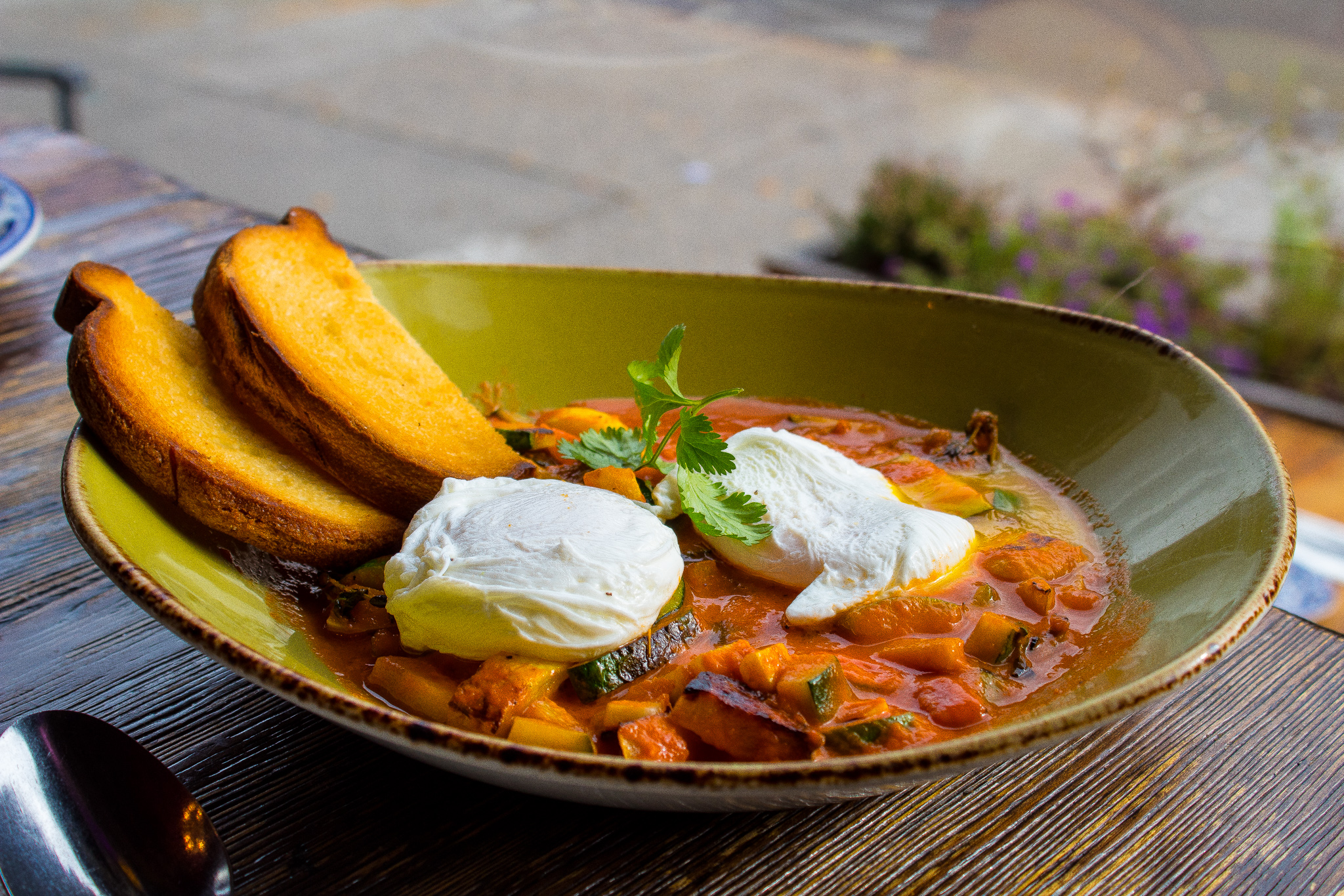 Calabacitas - Zucchini and yellow squash baked in roasted tomato sauce and served with toast and poached eggs