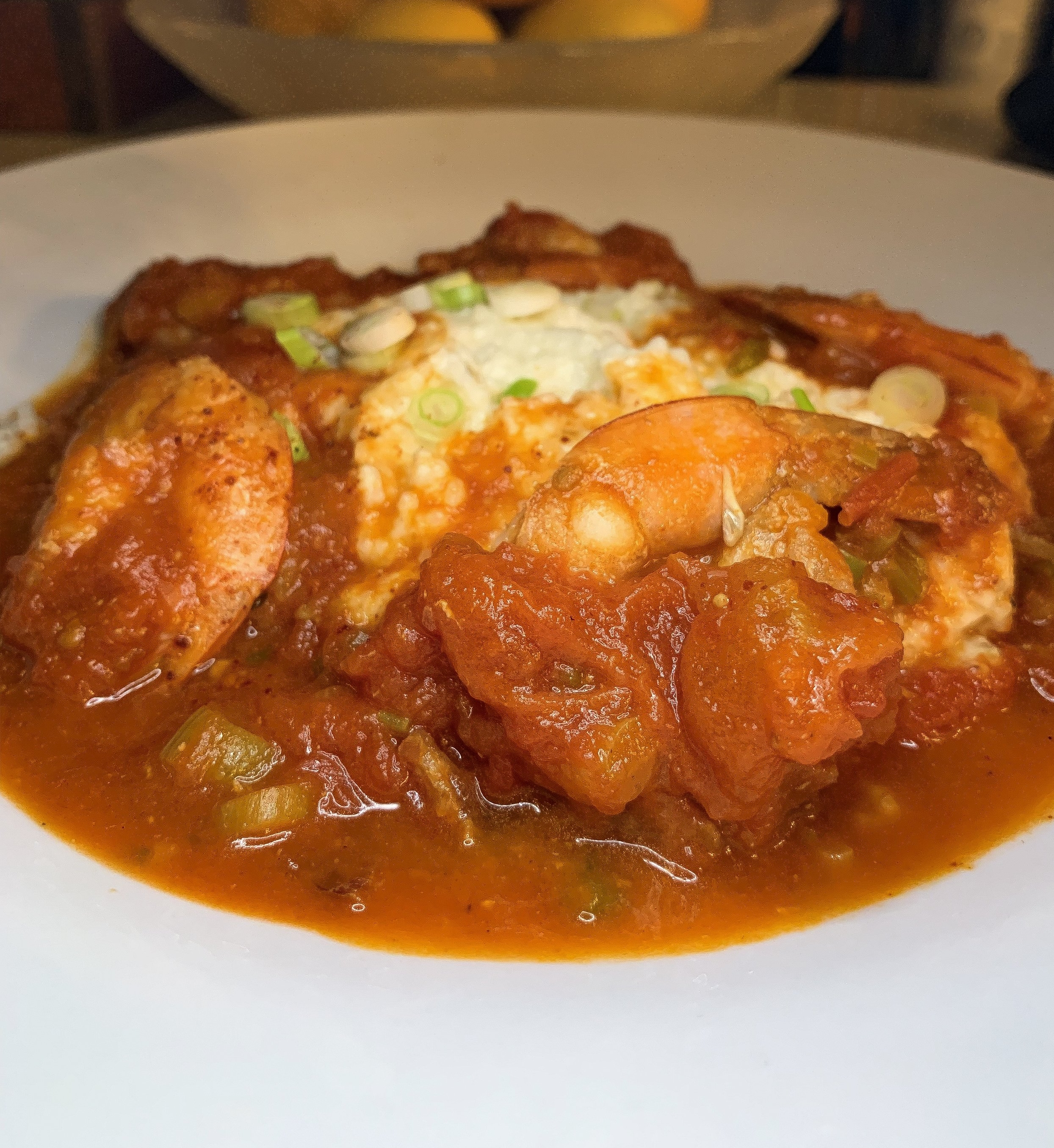 Lowcountry Shrimp and Grits - spit roasted pork, grits, tomatoes, scallions, roast shrimp broth