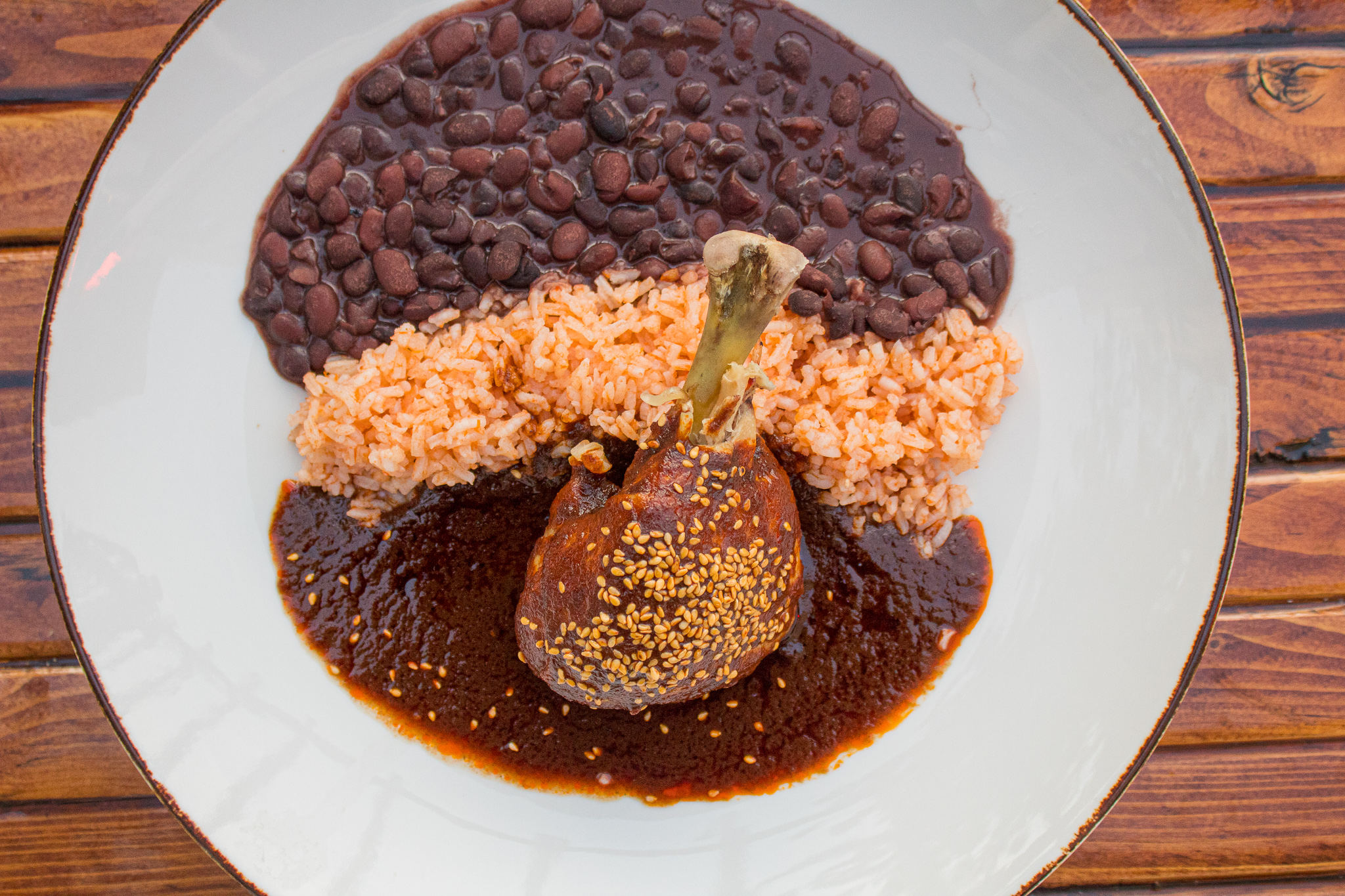 Pollo con Mole Poblano - Slow Cooked Chicken Leg with Red Rice, Beans, Mole Sauce, Sesame Seeds & Corn Tortillas