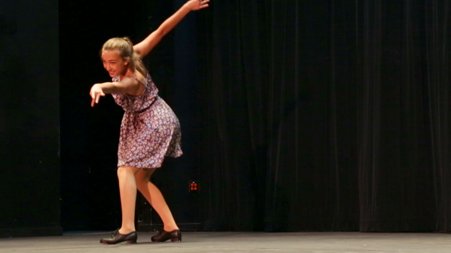 A student is doing a creative dance on stage