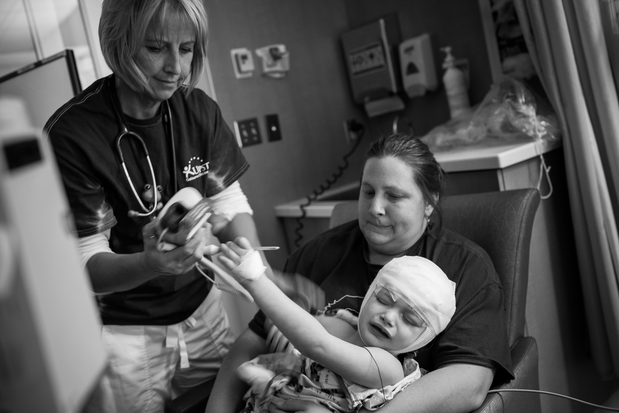 Arianna pushes away a nurse while recovering from brain surgery at Upstate Golisano Children's Hospital. During her most recent procedure, doctors removed three tubers from her brain.