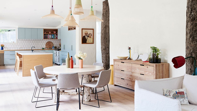 Soft upholstered chairs look inviting around this rustic dining setting, framed with an eclectic collection of PET lights overhead, in the former home of  Chris and Arabella Wilson . Table by  Mark Tuckey , retro tulip lamps from  1stDibs , Aga stove from  Aga Australia , and  PET  lamps. Photo –  Eve Wilson . Production – Lucy Feagins / The Design Files.
