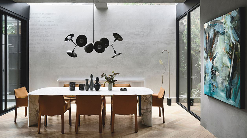 The grand dining space in  the home of Bear Agushi  in Armadale, designed by  Workroom , with interior decoration and styling by  Simone Haag.  Cab chairs Cassina from  Space Furniture,  and  Giffin Design  pendant lights. Wind chime by  Agustina Bottoni . Artwork 'Riven' by  Ian Rayer Smith , purchased from  Otomys Gallery . Marble table sourced by Simone from Italy. Photo –  Derek Swalwell.  Styling –  Simone Haag.