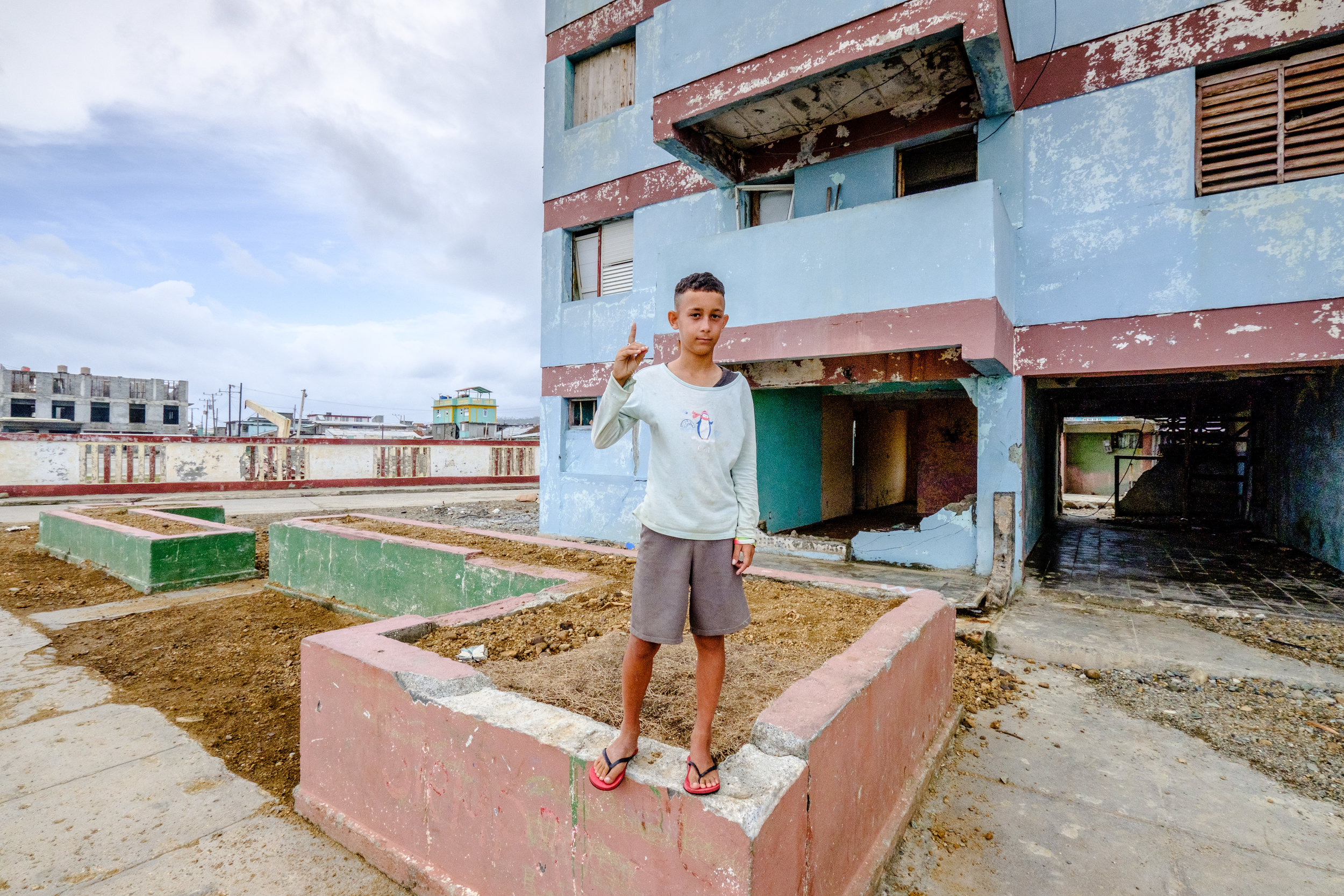 """Gelmis in front of his building. Secure in their faith, many of the Christian Deaf in Cuba will pose for a picture with the Cuban sign for """"God"""". (Letter """"d"""" in American Sign Language)"""