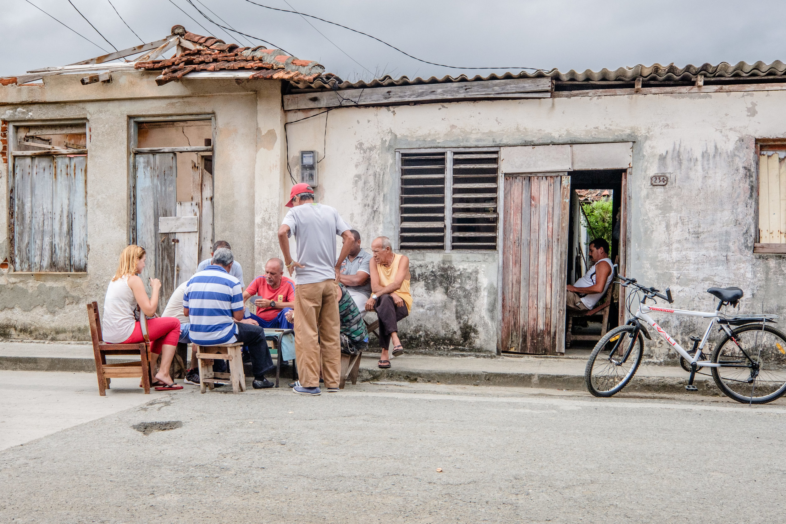 Neighbors playing a friendly game of cards on a Baracoa street outside the home of one of the Deaf youths we met with.