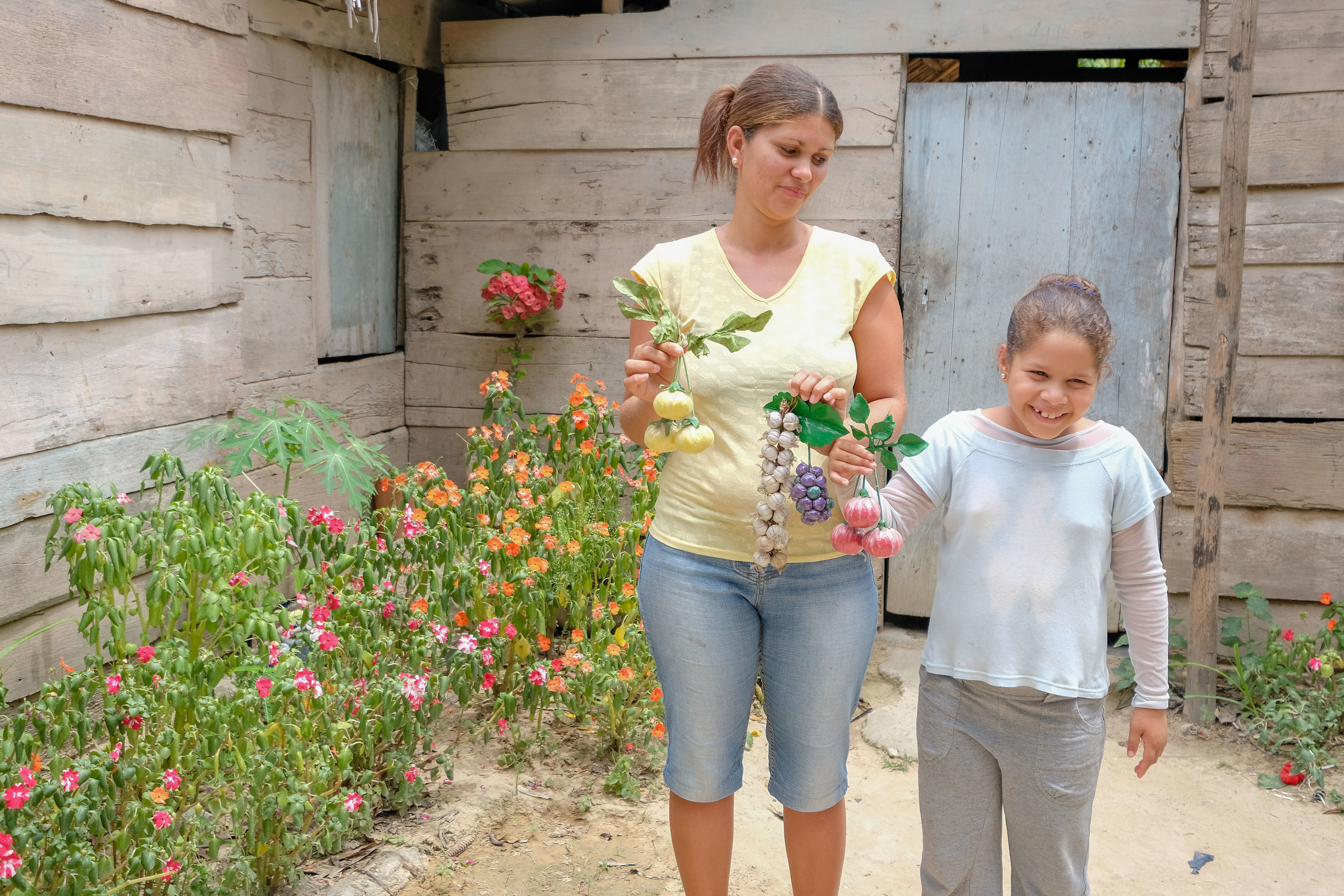 Yuneiris and Noemi posing in front of her flower garden, with recycled crafts she made.