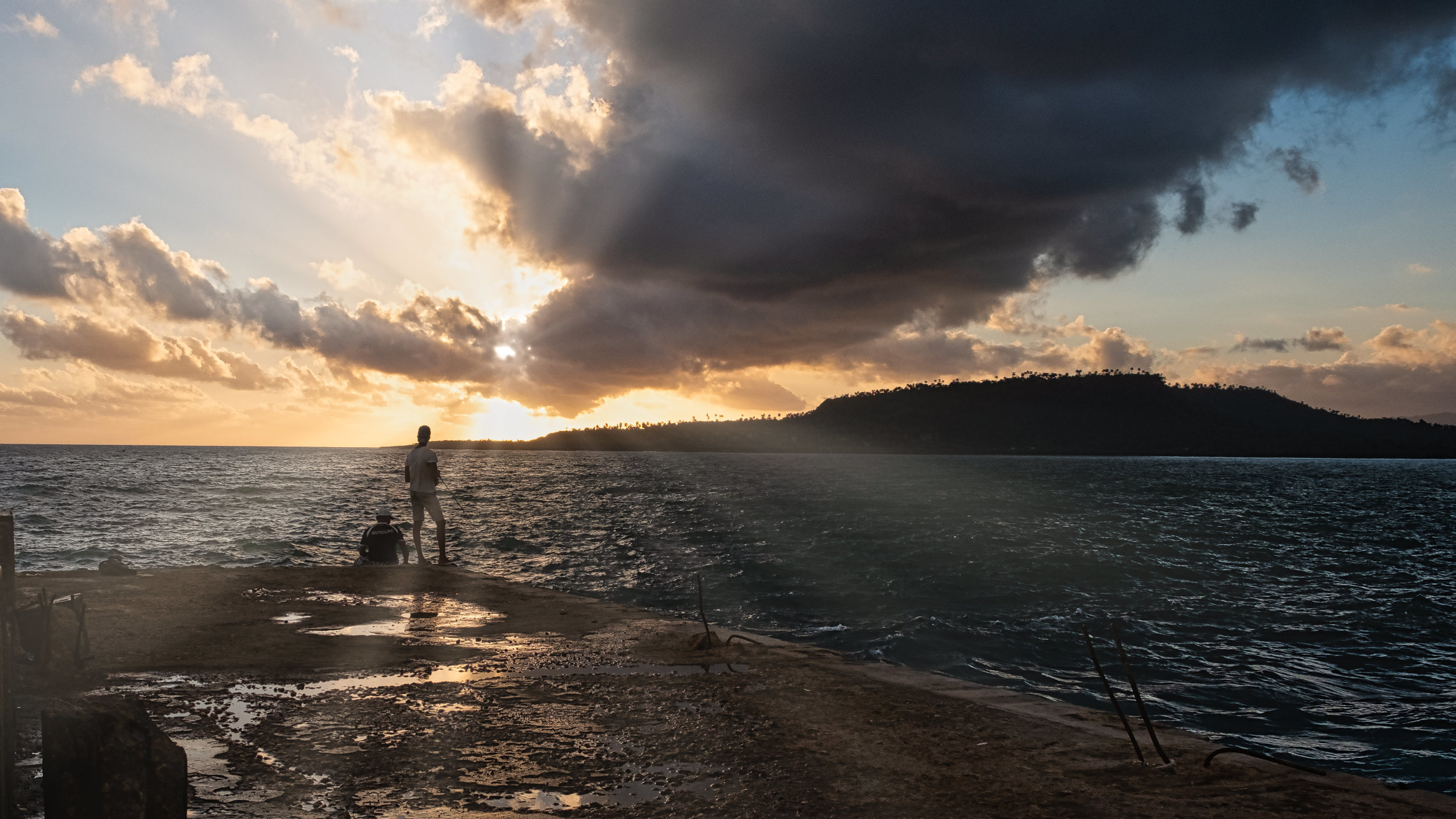 Sunrise Fishing off a Baracoa Pier. These Cuban men are hoping to catch breakfast, which might be their families only protein for the day.
