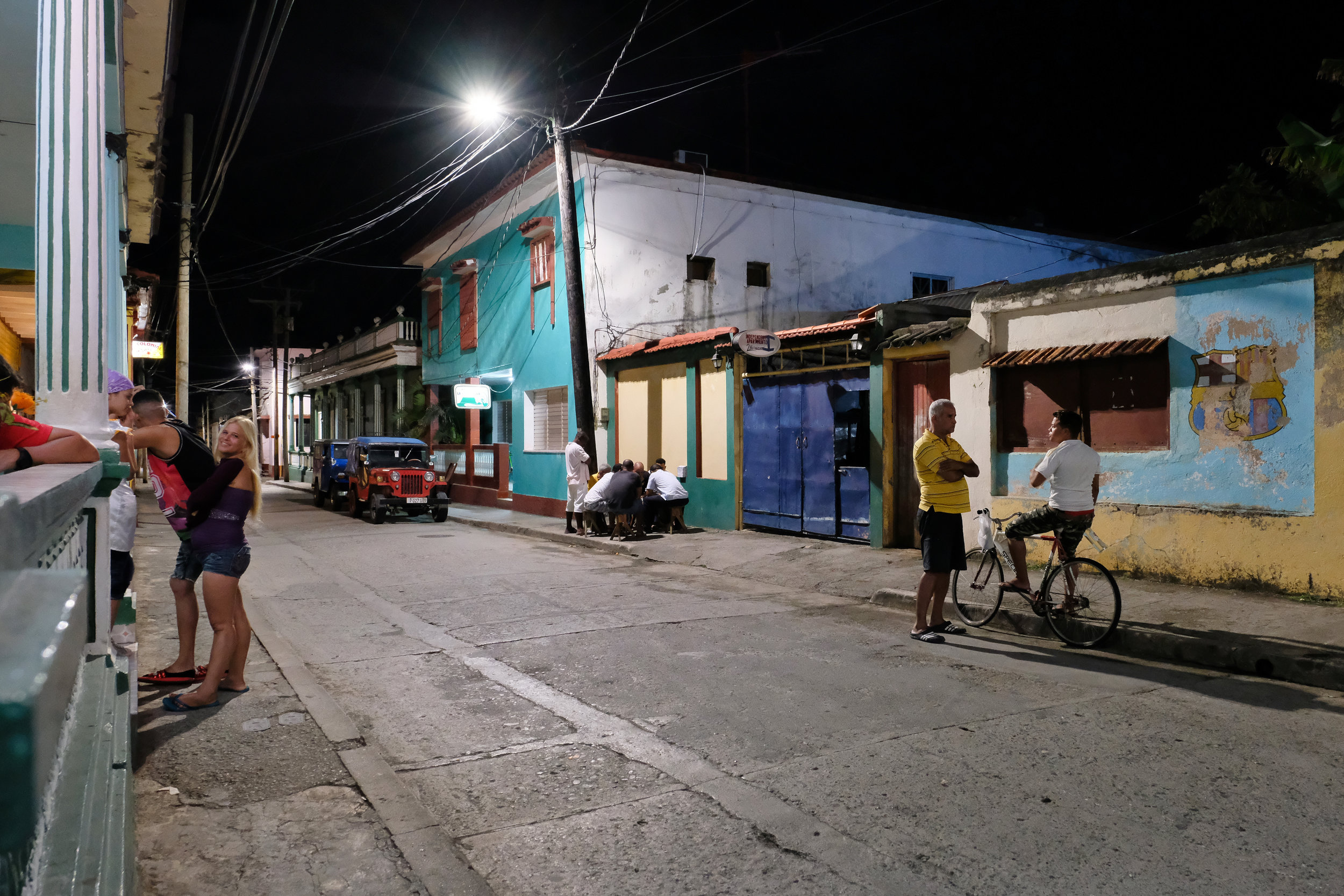 Baracoa Night Life away from the tourist area. Men huddled under street lamps playing Dominos or Chess (as these guys are) is a common sight.