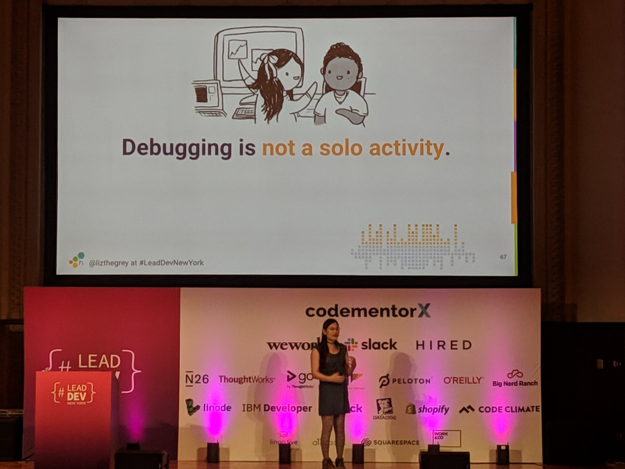 """Liz's slide tells us that """"Debugging is not a solo activity."""" Cute image of people debugging together by the extraordinarily talented  @emilywithcurls."""