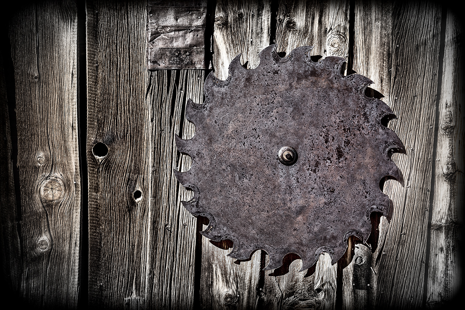 Graphic image of antique saw blade hanging on weathered wood.