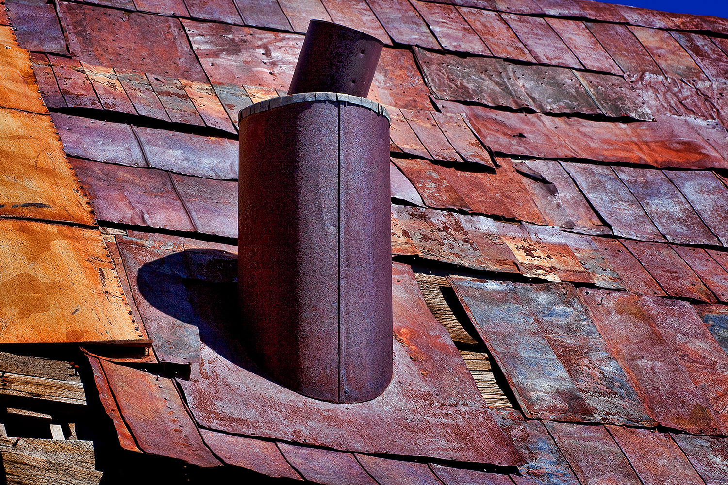 Rustic beauty of a rusty tin roof with smokestack on an old house at Bodie Ghost Town.