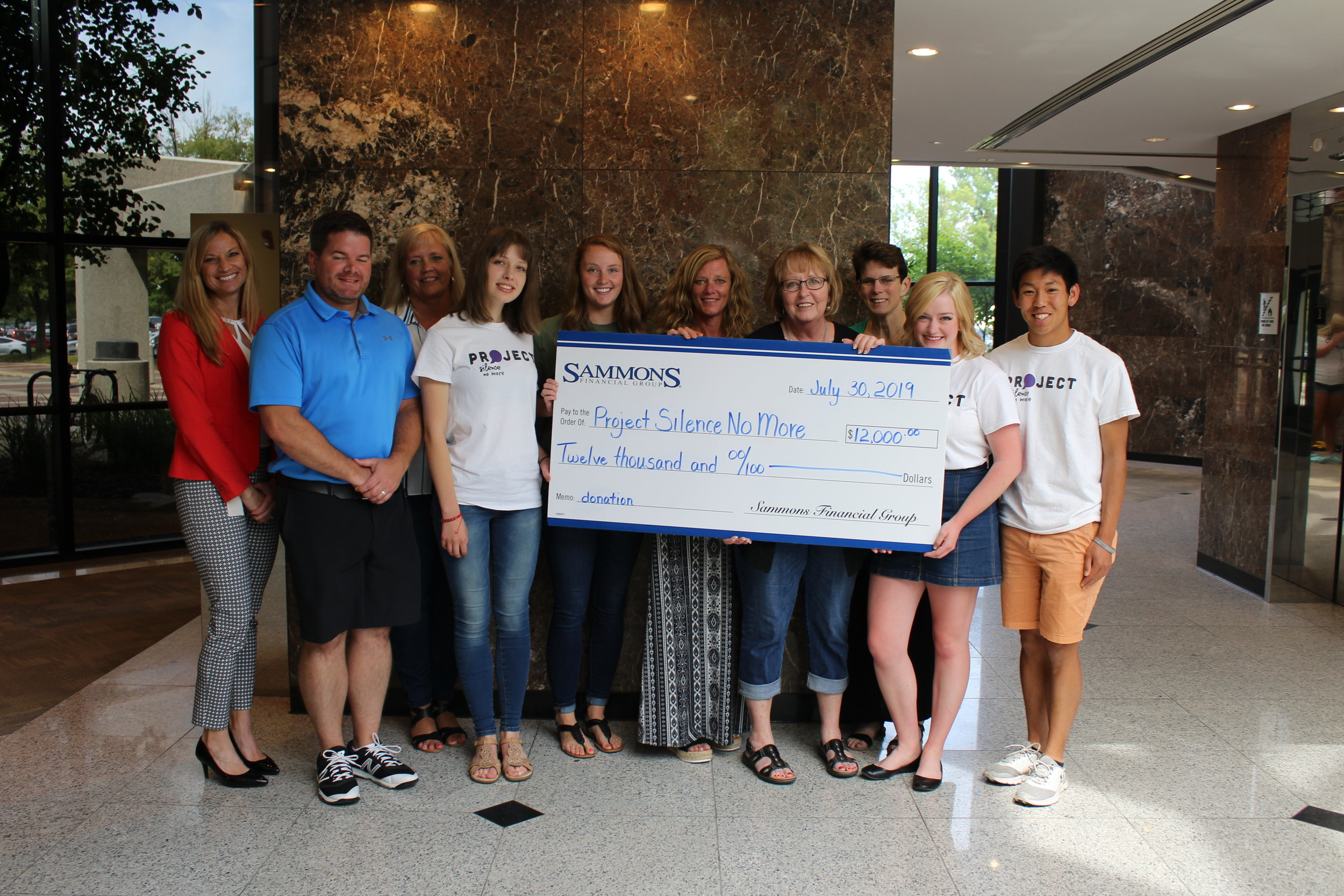 Presentation of the check by the community outreach committee at Sammons Financial to Project Silence No More