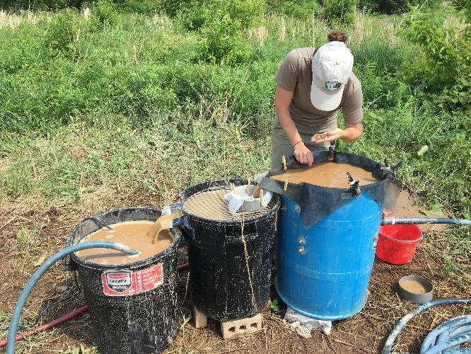 figure 1. alex glass conducting flotation by placing soil samples into the large tank. carbonized organic material floats to the surface and are collected in the second tank. water then flows to the third tank, which contains a pump, to be recirculated back to the first tank.