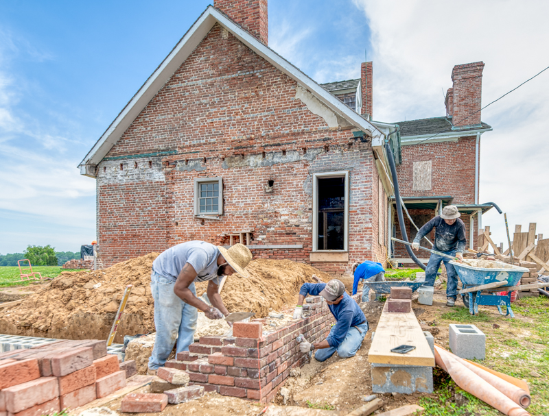 masons reconstructing the brick walls of the 1784 kitchen. photo by Pete Albert
