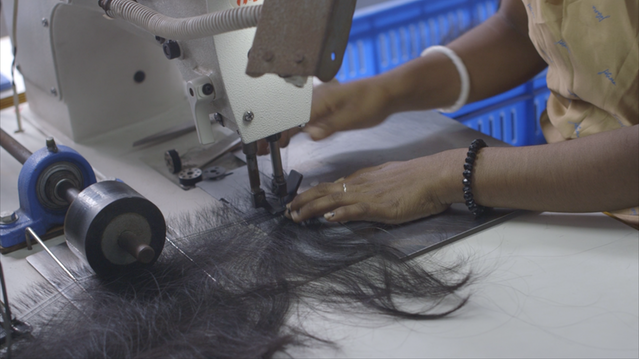 Indian woman sewing a human hair weft for a wig